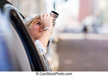 Turista sacando fotos en un coche con cámara
