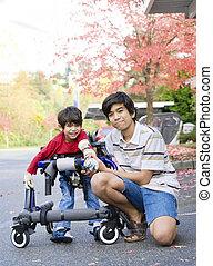 Un adolescente con un hermanito discapacitado paseando