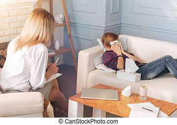 Un adolescente deprimido llorando mientras hablaba con su psicólogo