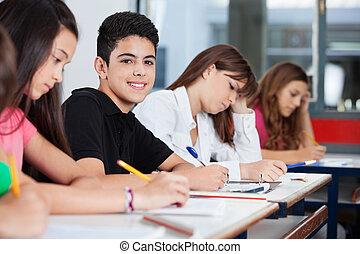Un adolescente sentado con amigos escribiendo en el escritorio