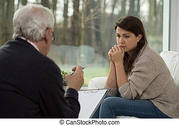 Un adolescente triste hablando con un psicólogo