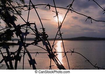 Un alambre de púas. Sunset. Ban