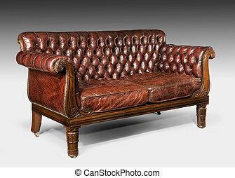 Un antiguo sofá de sofá cama de cuero marrón antiguo