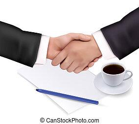 Un apretón de manos sobre papel y lápiz.
