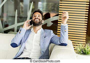 Un apuesto hombre de negocios hablando por teléfono móvil