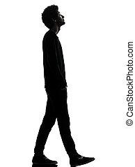Un apuesto joven africano caminando mirando silueta