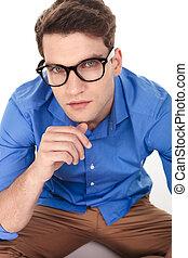 Un apuesto joven de la moda sentado en un fondo aislado