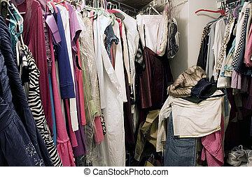 Un armario desorganizado lleno de ropa colgante