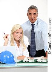 Un arquitecto y su asistente detrás de un modelo de distrito