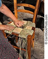 Un arte tradicional italiano: mujer haciendo un asiento de paja para una silla de madera