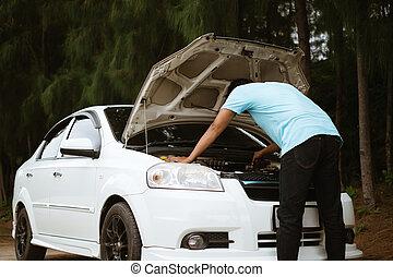 Un asiático estresado mirando el motor de un coche roto