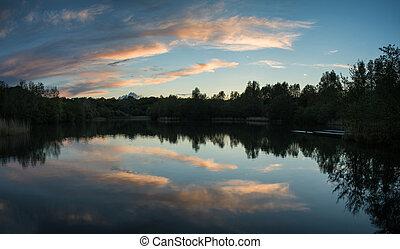Un atardecer vibrante de verano reflejado en aguas tranquilas del lago