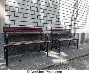 Un banco de madera marrón o una silla delante de la oficina con pared de ladrillo