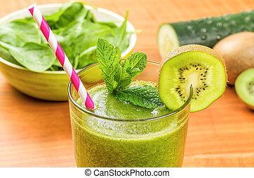 Un batido verde con una pajita para beber y ingredientes frescos