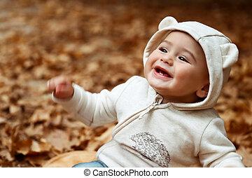 Un bebé alegre en el bosque de otoño