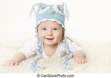 Un bebé feliz con sombrero azul tejido, un niño levantando la cabeza, sonriendo retrato infantil, de seis meses