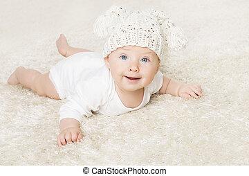 Un bebé feliz con sombrero tejido blanco arrastrándose en una manta blanca, retrato de niño, niño sonriente de seis meses