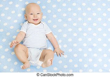 Un bebé feliz tumbado en el fondo de alfombra azul, con vistas al cielo, niño sonriente vestido con traje de baño en una manta de seis meses