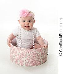 Un bebé precioso sentado en una caja de sombreros