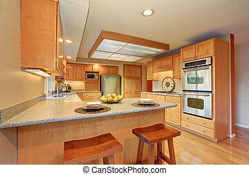 Un brillante interior de cocina de madera con aparatos de acero.