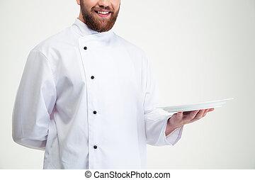Un chef feliz con un plato vacío