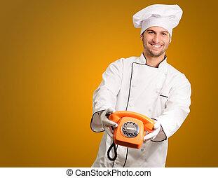 Un chef feliz sosteniendo el teléfono