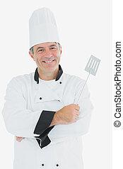 Un chef feliz sosteniendo espátula