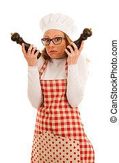 Un chef inseguro con sal y pimienta molido aislado sobre blanco