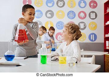Un chico agradable hablando con su compañero de equipo durante la clase de química