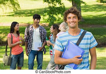 Un chico con amigos universitarios en el campus