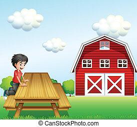 Un chico en la mesa cerca del establo