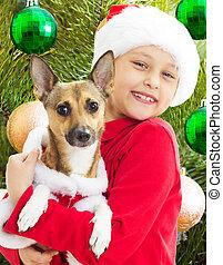 Un chico encantador con ropa de Navidad sosteniendo a su perro