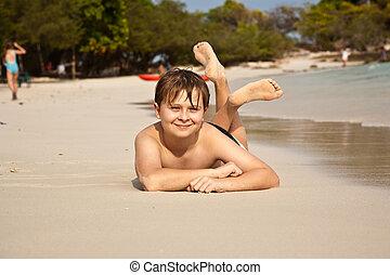 Un chico feliz tirado en la playa