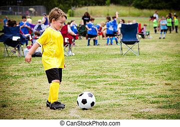 Un chico joven jugando al fútbol durante el juego de la liga organizada