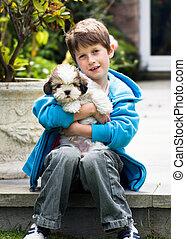 Un chico joven sosteniendo un cachorro de apso