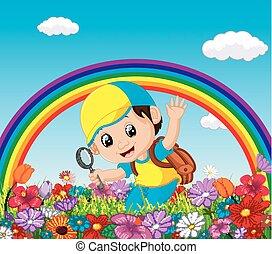Un chico lindo sosteniendo una lupa en un jardín de flores con arco iris