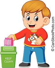 Un chico mantiene un ambiente limpio por basura en la basura