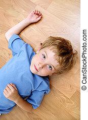 Un chico serio tirado en el suelo