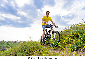 Un ciclista montando en bicicleta en un hermoso sendero de montaña primavera