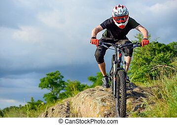 Un ciclista profesional montando en bicicleta en el hermoso sendero de la montaña de primavera. Deportes extremos