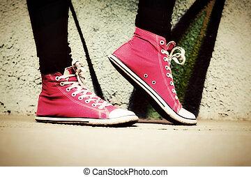 Un cierre de zapatillas rosas usadas por un adolescente.