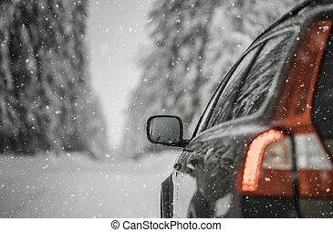 Un coche en una carretera de invierno nevada entre los bosques