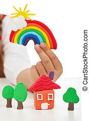 Un concepto de ambiente limpio: manos de niño con figuras coloridas hechas de arcilla