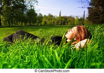 Un concepto despreocupado, una mujer que se relaja al aire libre en la hierba