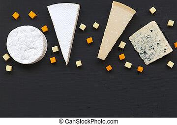 Un conjunto de diferentes tipos de queso en fondo oscuro. Comida romántica. Planta. Desde arriba, desde arriba. Copia espacio.