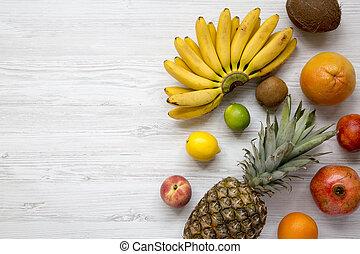Un conjunto de frutas tropicales frescas en un fondo blanco de madera, desde arriba. Copia espacio. Planta.