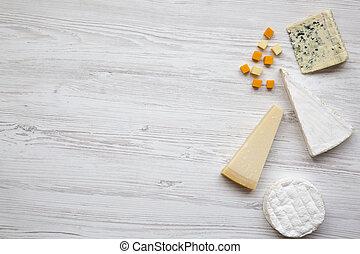 Un conjunto de quesos diferentes en un fondo de madera blanco con espacio de copia, vista superior. Comida para el vino. De plano, desde arriba.