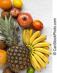 Un conjunto de varias frutas tropicales en un fondo blanco de madera, desde arriba. Planta plana, arriba, vista superior.
