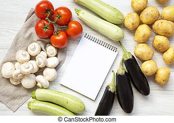 Un conjunto de varias verduras con cuaderno en un fondo blanco de madera, vista desde arriba. Arriba, tendido plano.