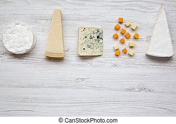 Un conjunto de varios quesos en un fondo blanco de madera con espacio de copia. Desde arriba, plano.